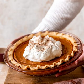 Hands holding up a sweet potato pie topped with fluffy whipped cream and sprinkled with ground nutmeg.
