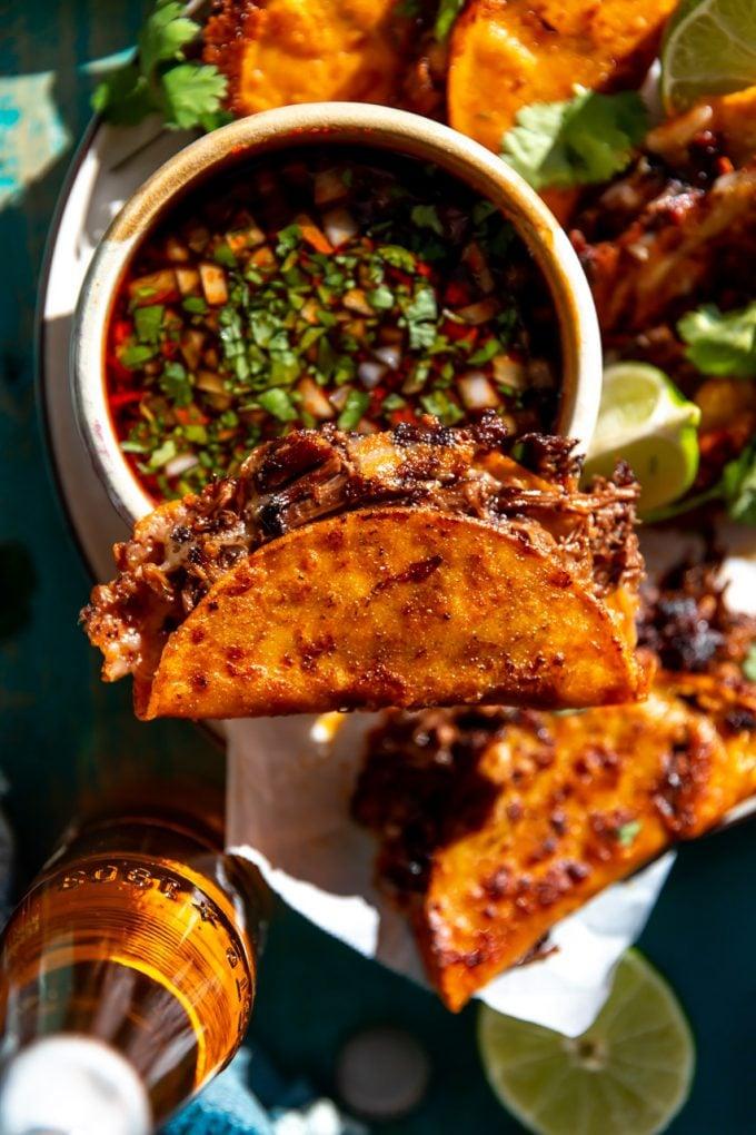 Birria Taco balanciert auf einer Schüssel Consommé.