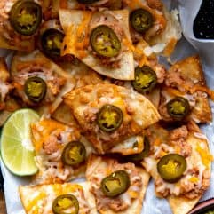 Texas Nachos served with some lime wedges and guacamole.
