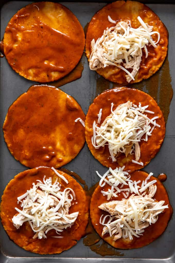 Corn tortillas smothered with enchilada sauce and topped with shredded chicken and cheese.