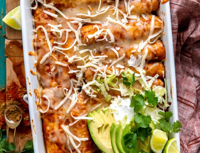 White baking dish filled with chicken enchiladas and topped with sliced avocado, sour cream and fresh cilantro.