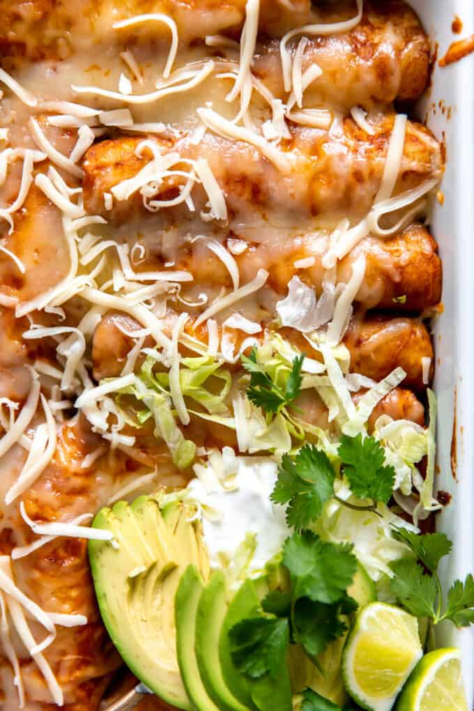 Up close view of enchiladas topped with melted cheese, sliced avocado, sour cream and lime wedges.