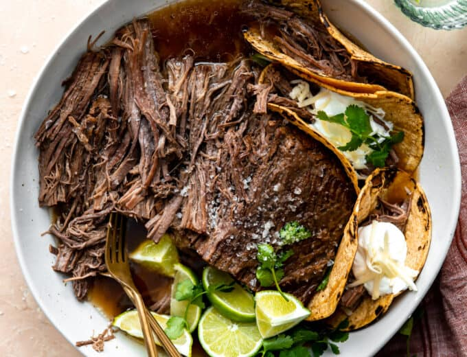Bowl filled with shredded Mexican brisket and corn tortillas for making tacos.