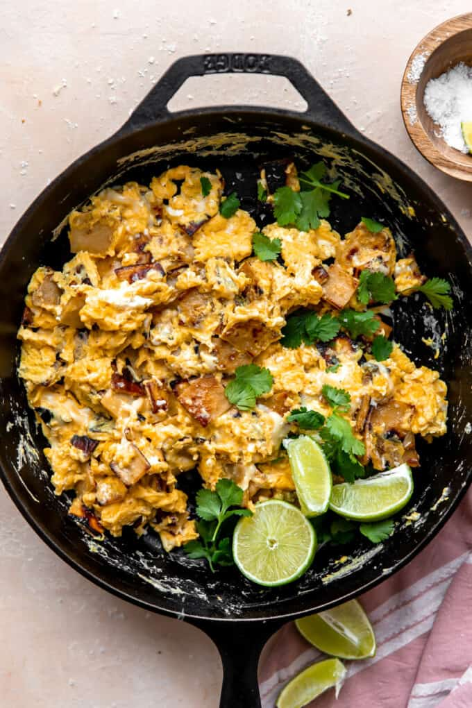 Skillet with scrambled eggs and tortillas with fresh cilantro garnish and lime wedges.