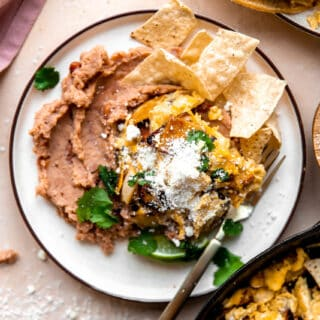 Overhead picture of Migas served over refried beans on a white plate.