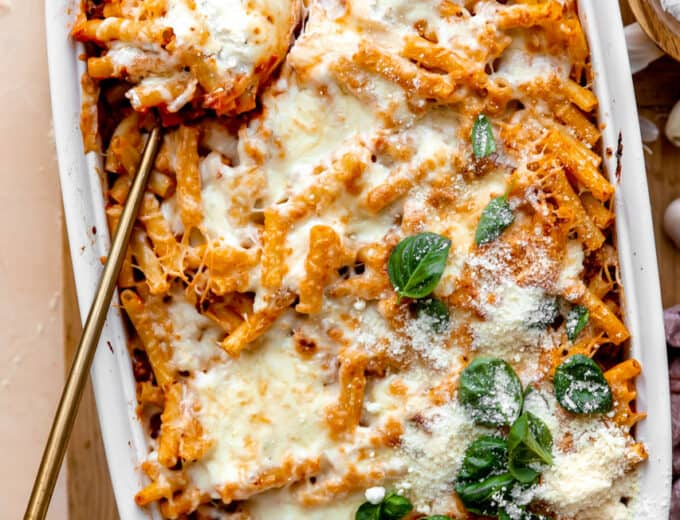 Spoon dishing into a baking dish filled with baked ziti, topped with melted cheese and basil leaves.
