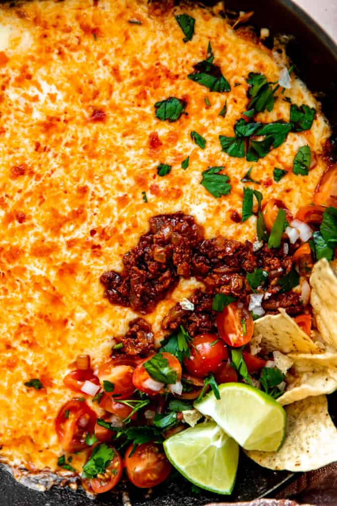 Up close view of queso funded. Showing melted cheese and chorizo, topped with pico de Gallo and cilantro.