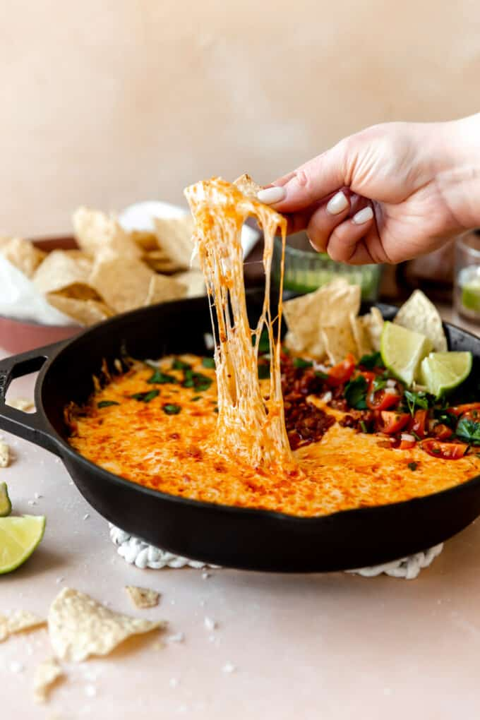 A chip dipping into a skillet of queso with chorizo.