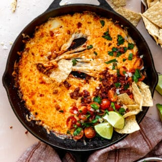 stretchy melted cheese in a skillet with chorizo and pico de Gallo.