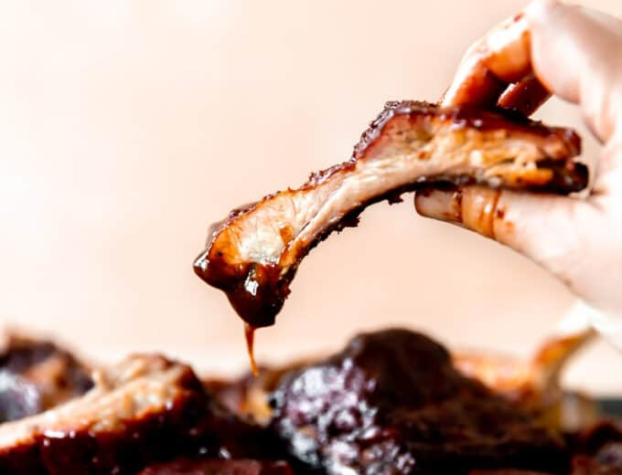 Hand picking up a smoked pork rib dipped in BBQ sauce.