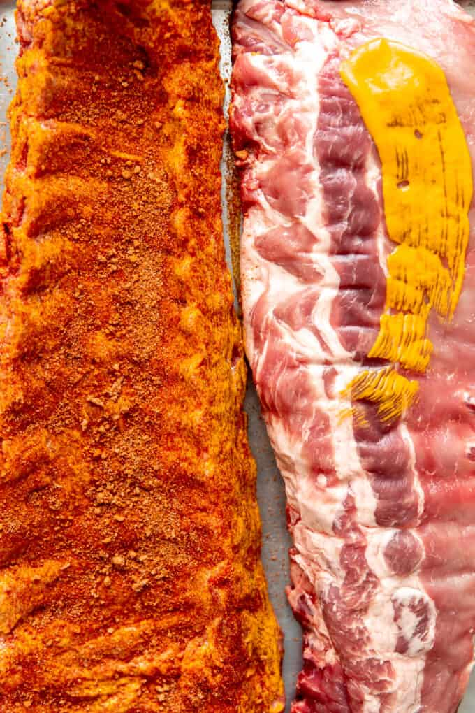 Pork ribs being slathered with mustard and a sweet and spicy rub.