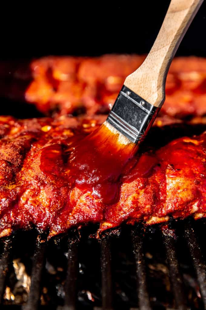 Brush dipped in BBQ sauce slathering pork ribs in a smoker.