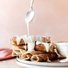 Stack of cinnamon tortillas being drizzled with cream cheese glaze.