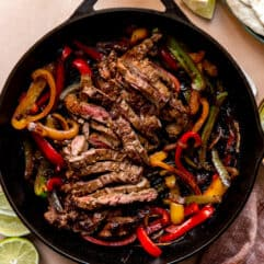 Large cast iron skillet filled with sliced grilled steak and grilled bell peppers and onions.