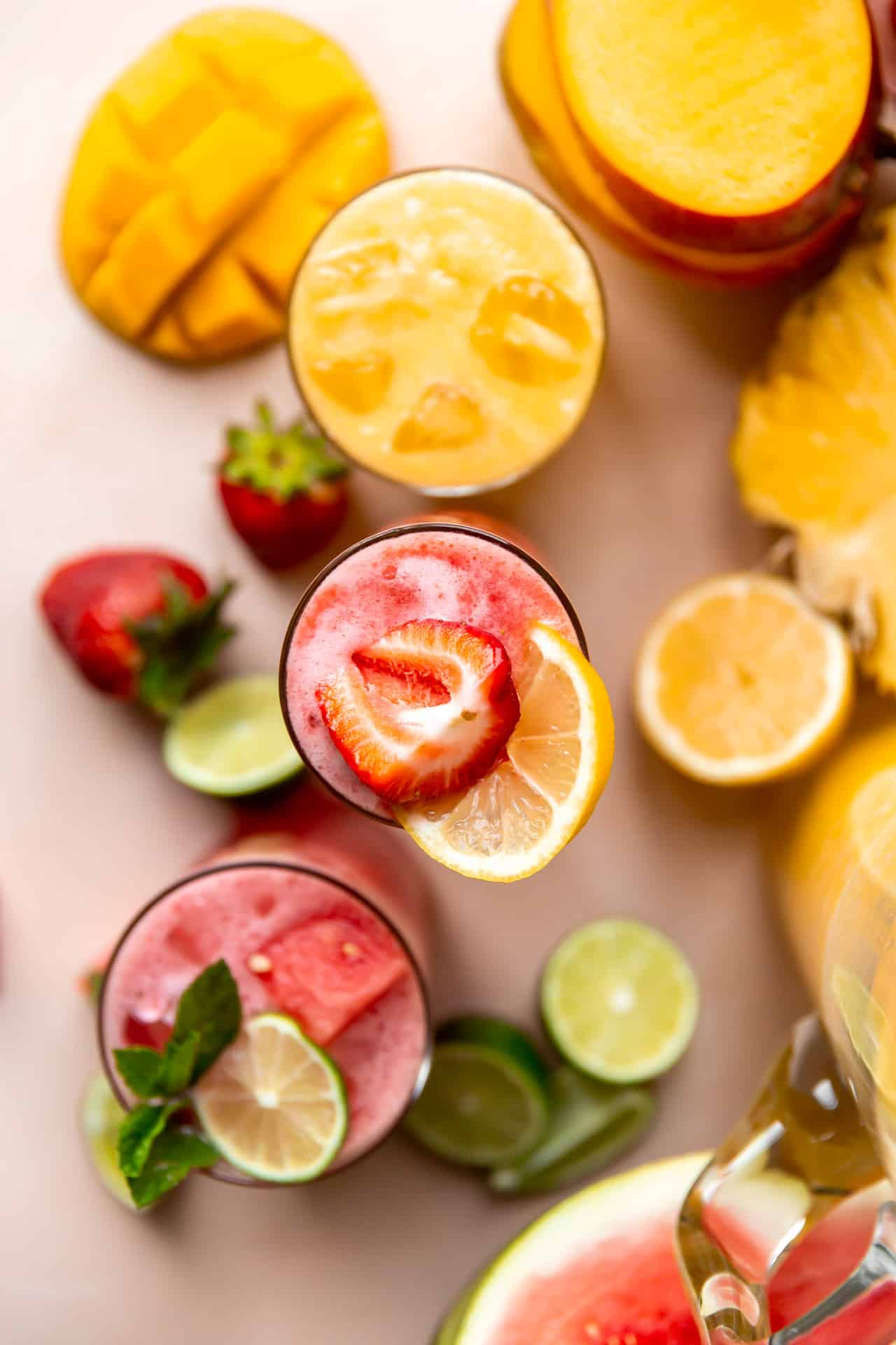 Overhead shot of cups of agua fresca on a counter surrounded by fruits.
