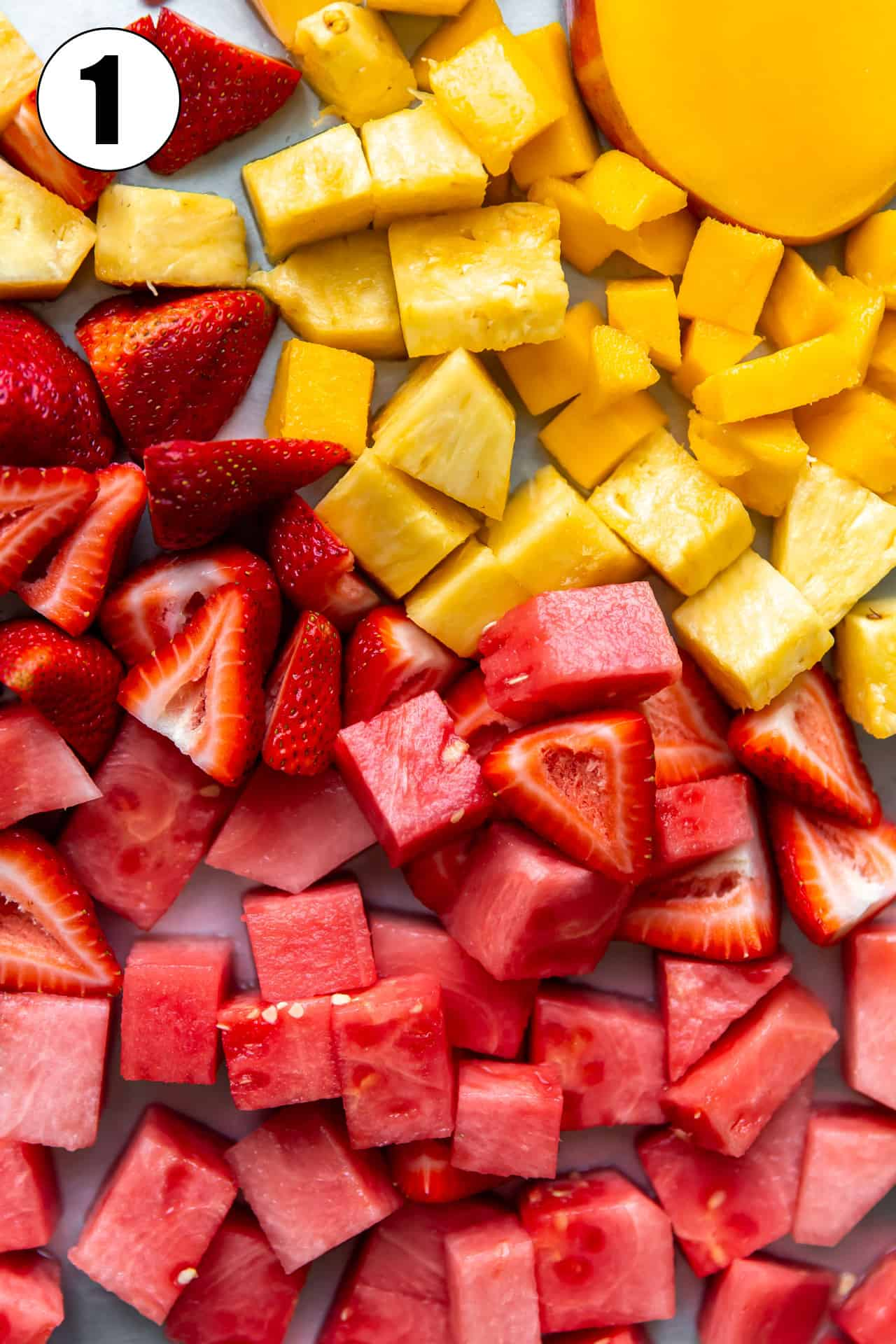 Chopped fruits laid spread out, watermelon, strawberry and mango.