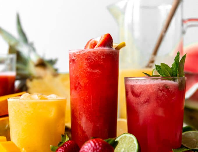 Glasses of agua fresca lined up showing strawberry, watermelon and a pineapple mango.