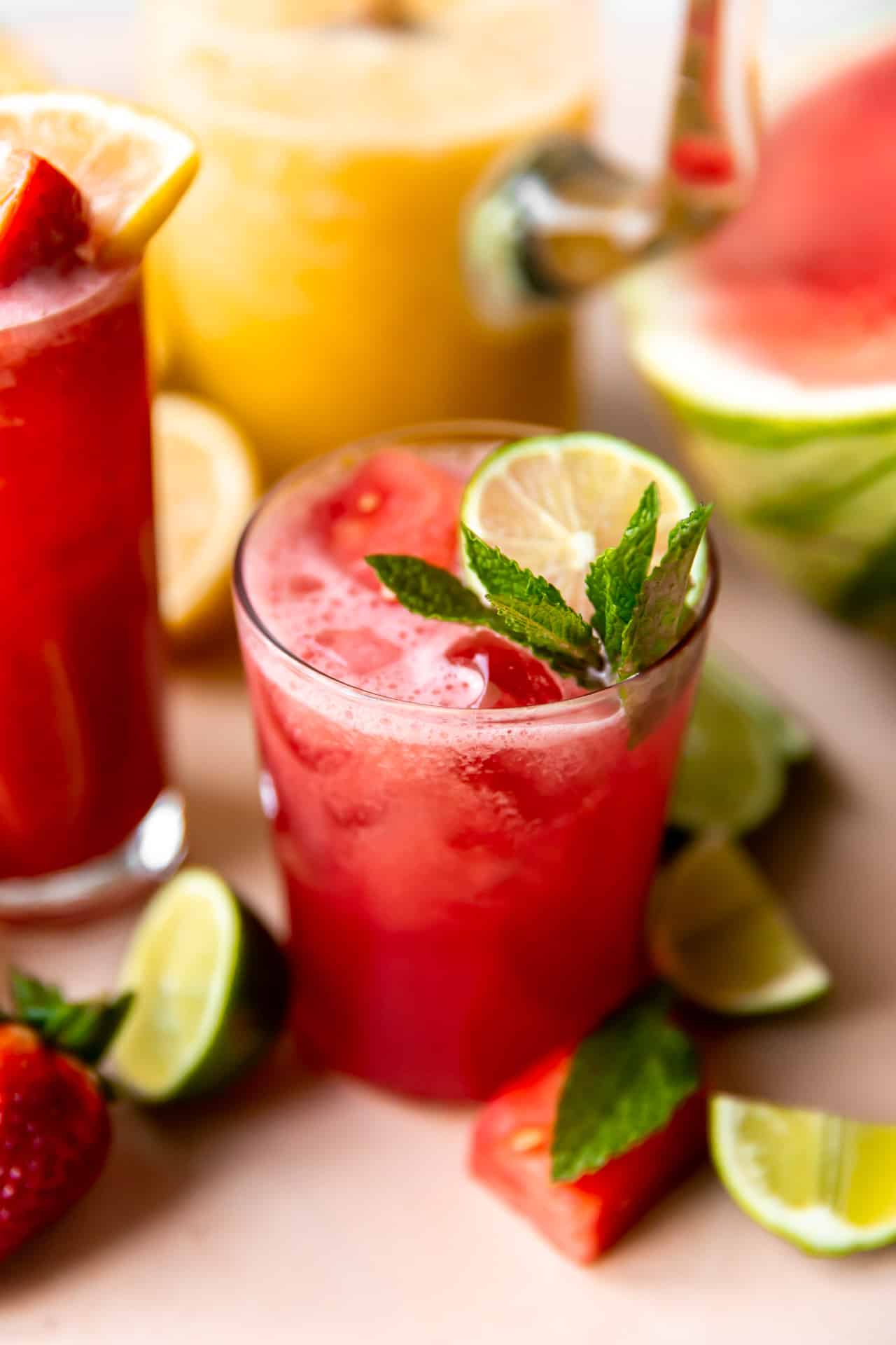 Glass of watermelon agua fresca garnished with mint and lime.