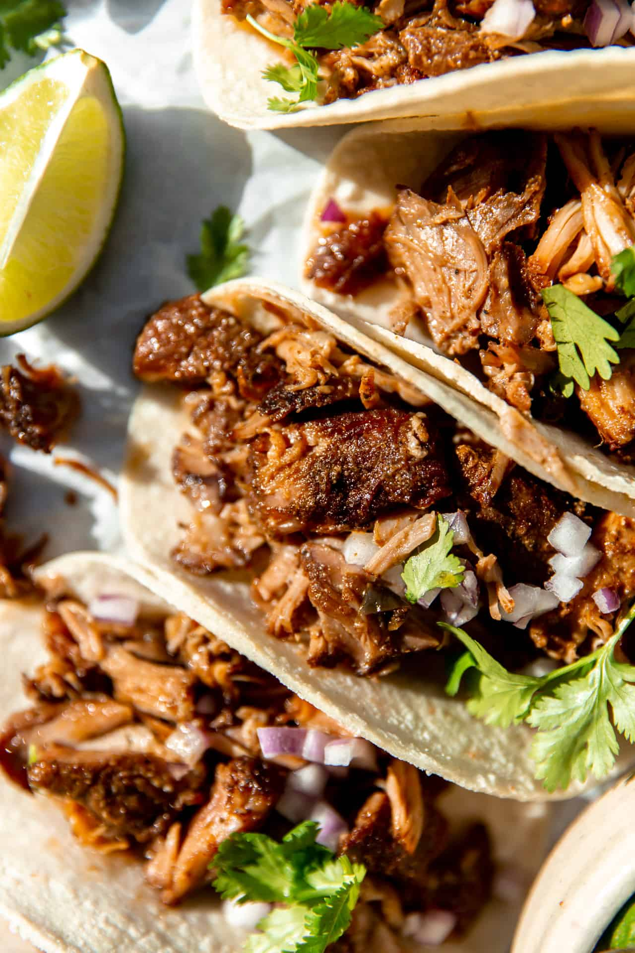Up close view of carnitas tacos showing crispy pieces of pork in soft corn tortillas with cilantro and diced onion.