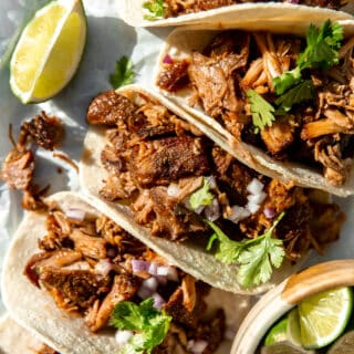 Carnitas Tacos lined up and topped with fresh cilantro, and diced red onion, lime wedges on the side.