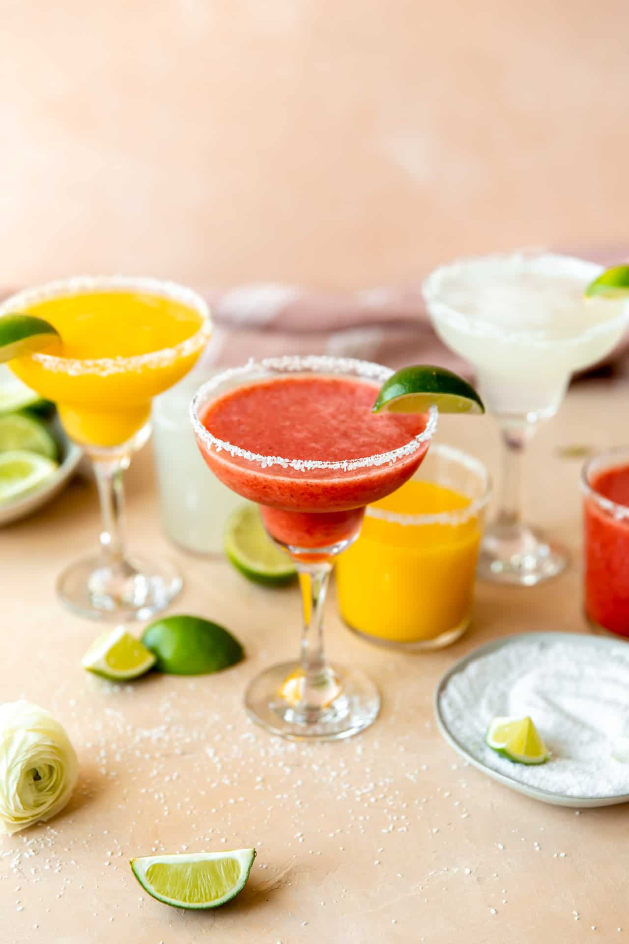 Frozen fruit margaritas lined up with mango, strawberry, and lime, with wedges of limes surrounding.