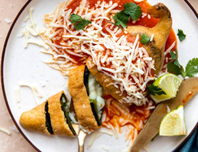 Plated Chile Rellenos with red sauce, sliced showing melted cheese inside.