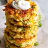 Stack of homemade corn fritters topped with a swirl of sour cream.