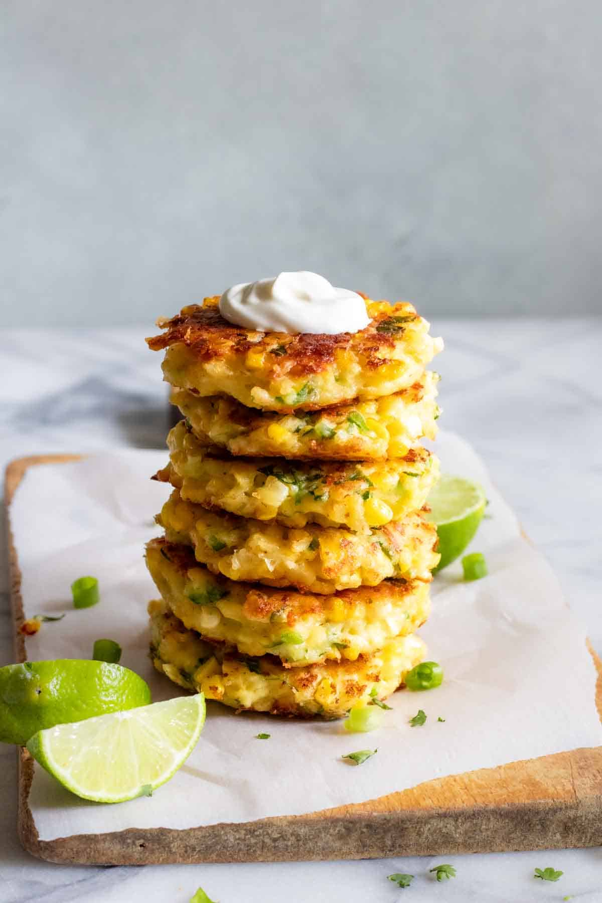 Stack of corn fritters on a wood cutting board all topped with sour cream.