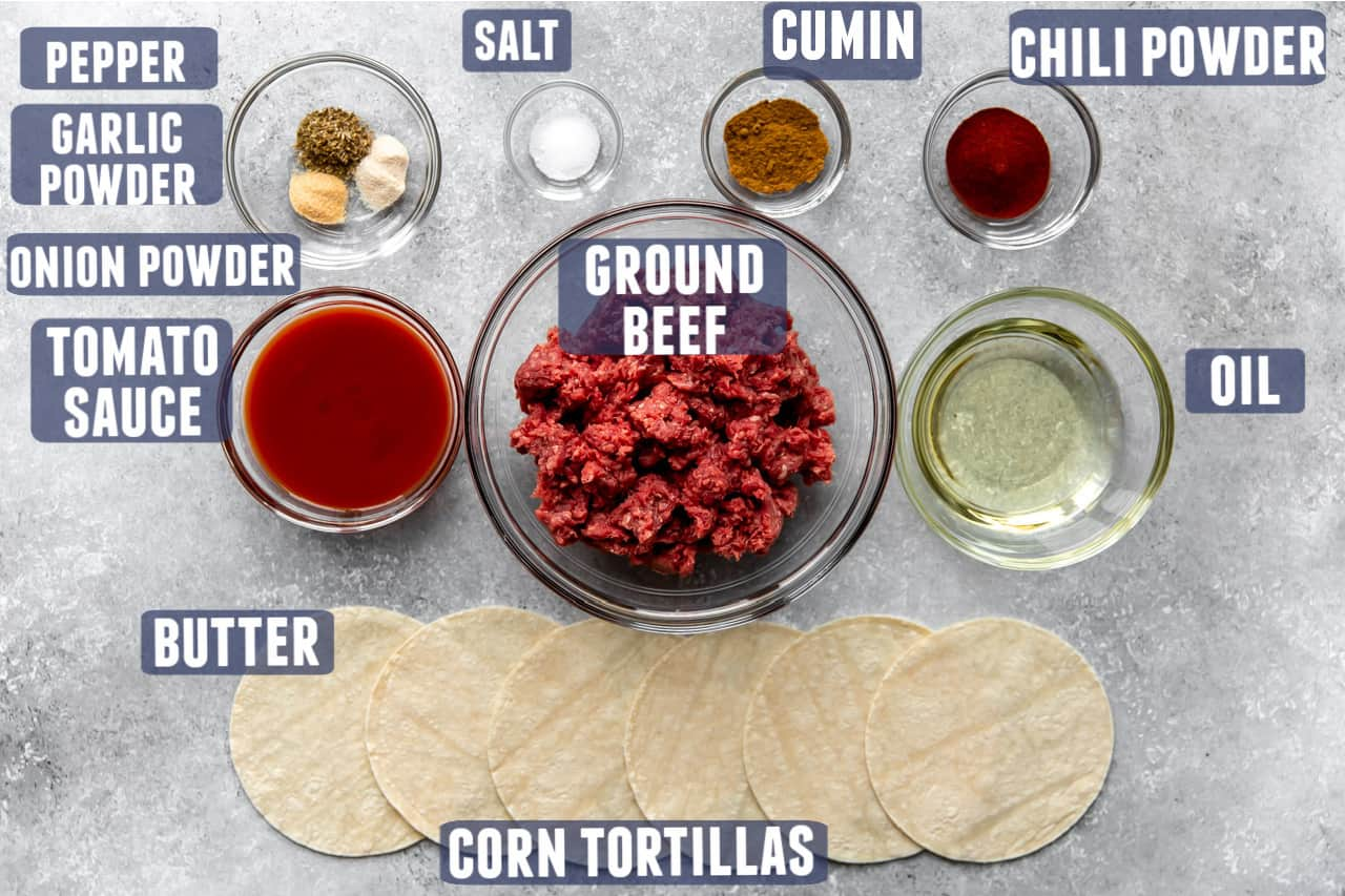 Ingredients needed to make ground beef taco meat and tacos laid on the counter.