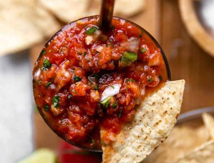 Overhead view of a jar of homemade sals with a tortilla chip being dipped in.