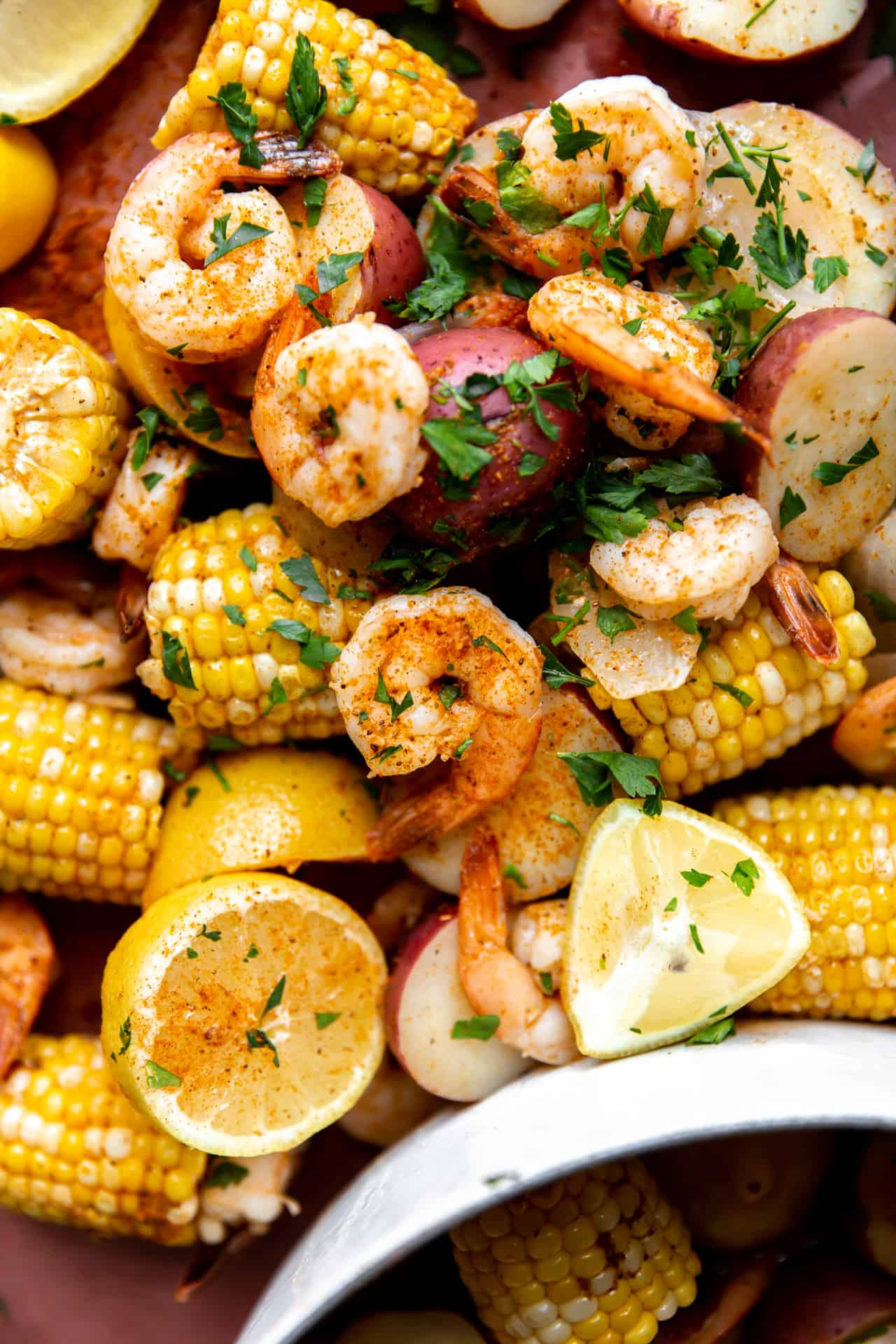Up close view of cooked shrimp boil topped with fresh lemon and chopped parsley.