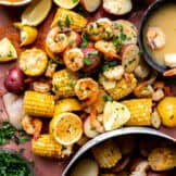 Shrimp boil spread out on butcher paper, with a side of old bay seasoning, beer and garlic butter.