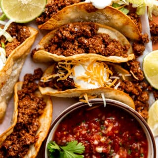 Plate of ground beef tacos on fried corn tortillas topped with sour cream and served with salsa.