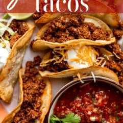 Ground beef tacos on a plate served with a bowl of salsa.
