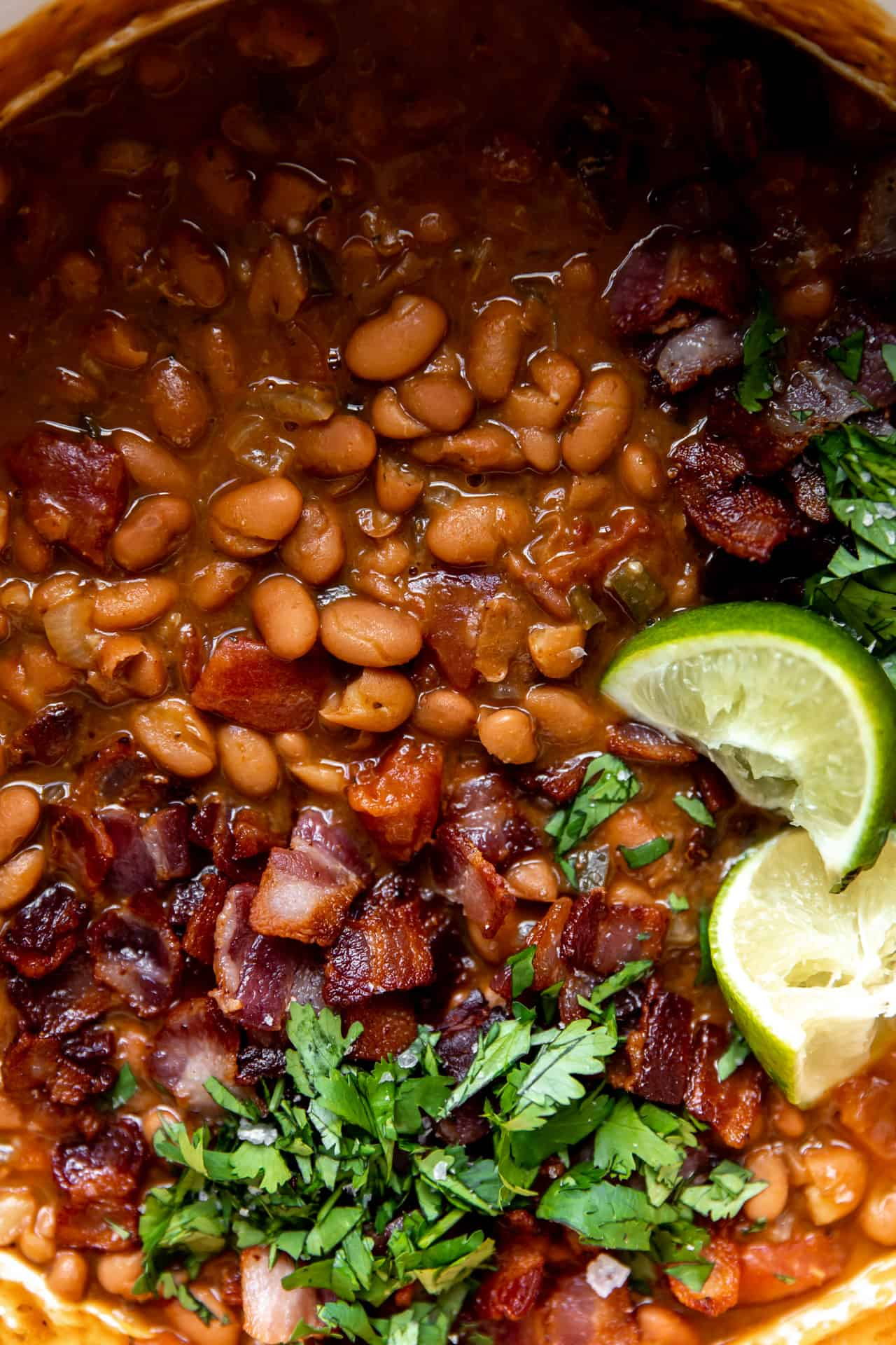 Up close view of cooked borracho beans topped with diced cilantro and lime wedges.