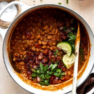 Dutch oven filled with cooked borracho beans topped with cilantro and lime wedges.
