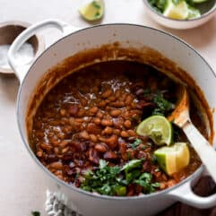 Pot filled with cooked borracho beans topped with cilantro and lime wedges.