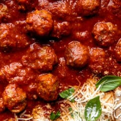 Up close view of meatballs simmered in red marinara sauce and topped with fresh parmesan.