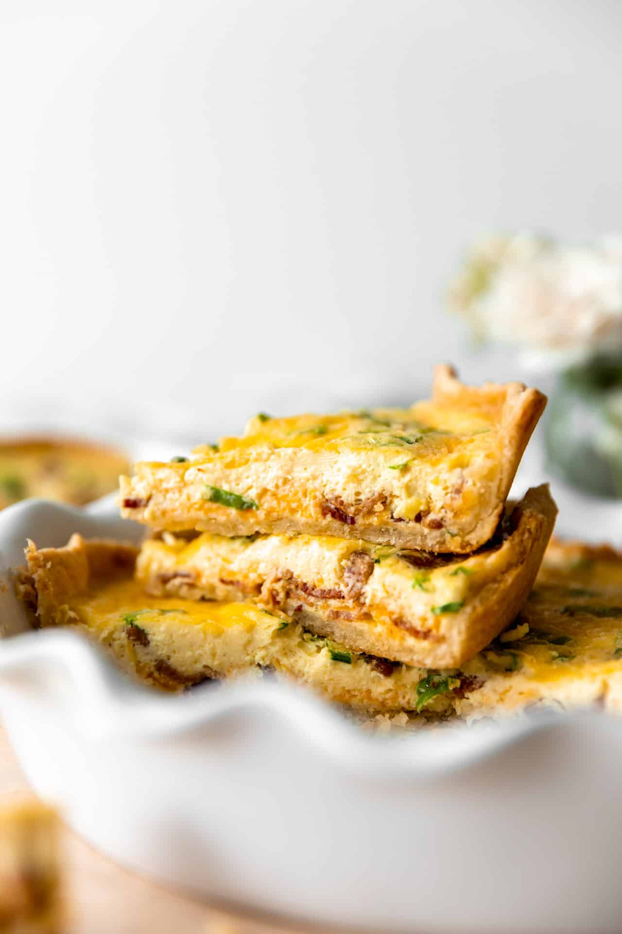 Stacked up slices of quiche in a pie dish.