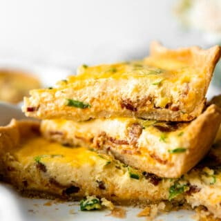 Sliced quiche stacked in a pie dish showing a custard egg filling and flakey pie crust.