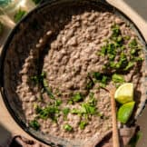 Skillet filled with refried beans, topped with cilantro and lime wedges.