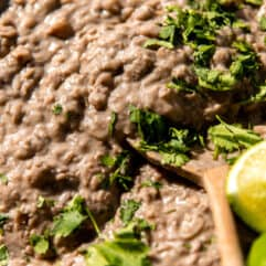 Spoon scooping up thick and creamy refried beans topped with cilantro and lime wedges.