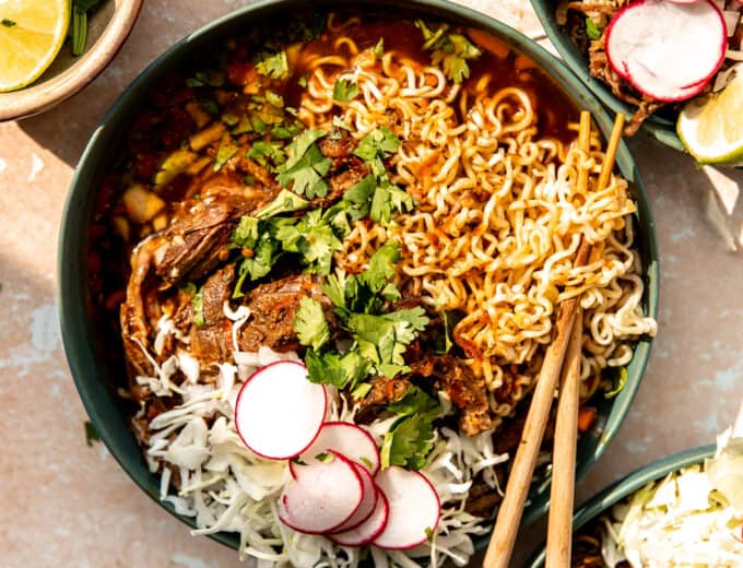 Bowl of birria ramen topped with shredded cabbage, sliced radishes and fresh cilantro.