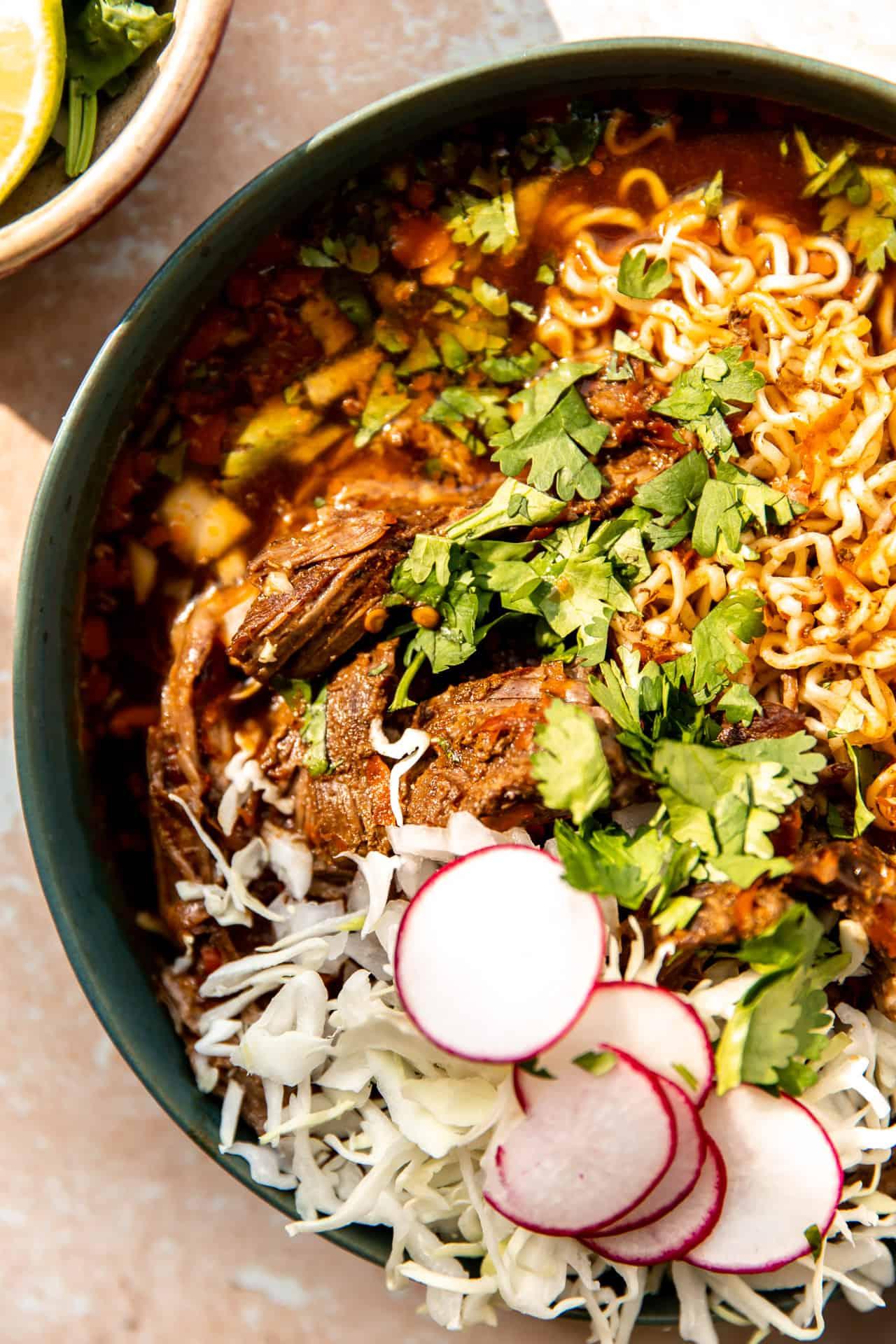 Close up view of chopped birria meat in a bowl of ramen.