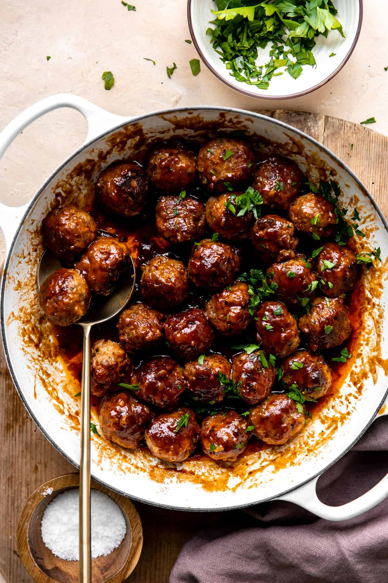 White skillet filled with bacon bourbon meatballs and topped with fresh parsley.