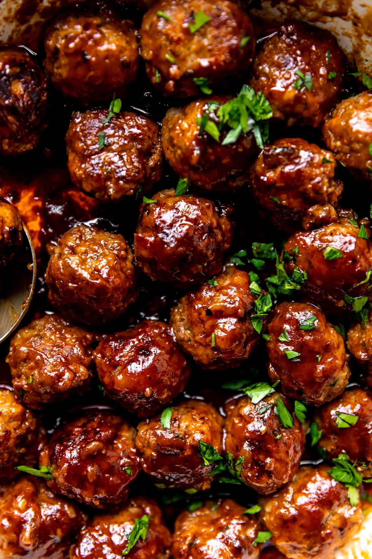 Up close view of a skillet filled with cooked bacon meatballs in a rich bourbon bbq sauce.
