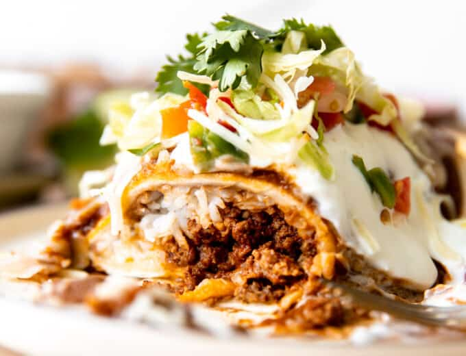 Wet burrito cut open to show it's filled with ground beef, cheese and rice. Topped with red sauce and sour cream.