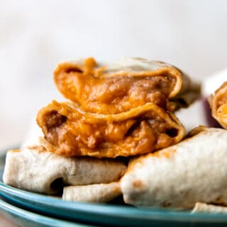Bean and cheese burritos stacked on a plate showing melty cheese and creamy beans with red sauce inside.