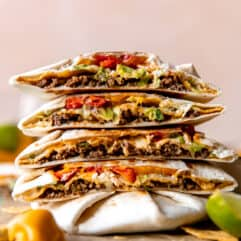 Stack of homemade Crunchwraps cut in half to show all the fillings inside.
