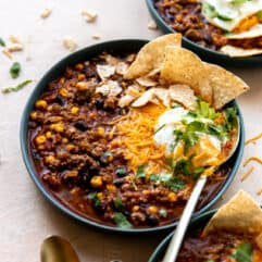 Bowl of taco soup served with cheese, sour cream and tortilla chips.